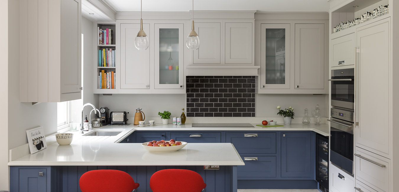 dark blue kitchen with red bar stools designed by interior designer Hilary White in Cobham, Surrey